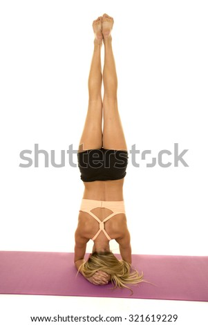 a woman standing on her head showing her strength. - stock photo