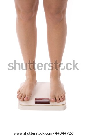 A woman standing on her scale to see about her weight loss. - stock photo