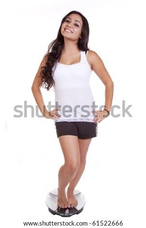 A woman standing on her weight scales with a happy expression on her face. - stock photo
