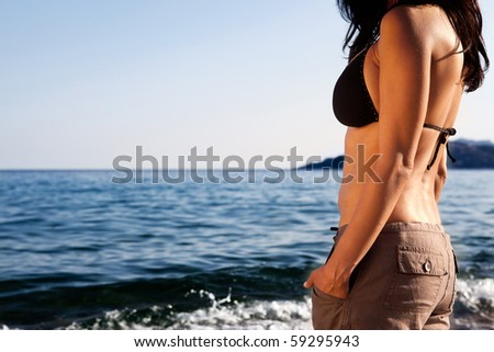 A woman standing on the beach looking out at the horizon - stock photo
