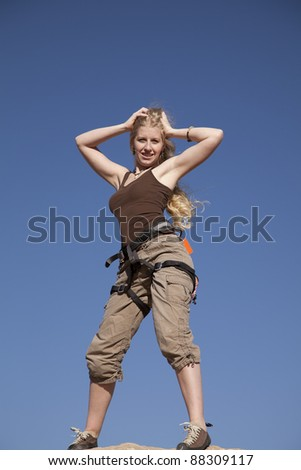 A woman standing on top of the rock she just climbed with a smile on her face. - stock photo