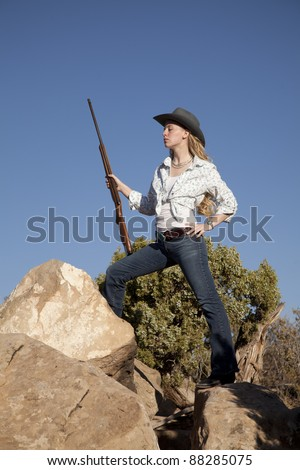 a woman standing up on top of rocks in her western wear holding a rifle. - stock photo