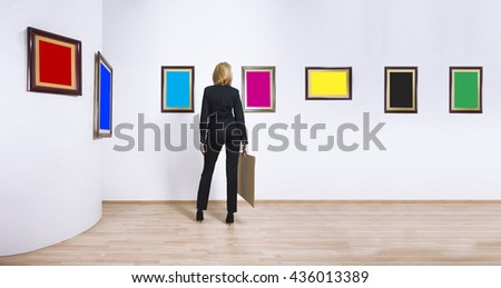 A woman standing with her back and looking at blank of CMYK and RGB color frames in art gallery.