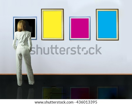 A woman standing with her back and looking at blank of color frames in art gallery. - stock photo