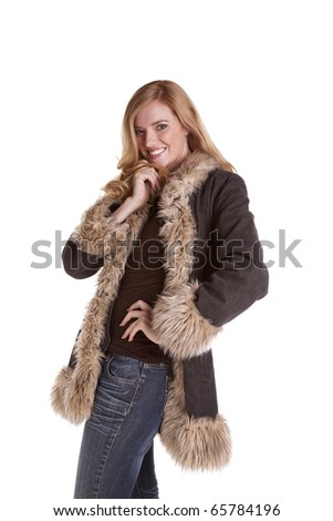 a woman standing with her hand on her hip while she is  wearing her fuzzy coat. - stock photo