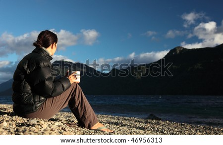 A woman stares into the distance on the shore of a Patagonian lake.