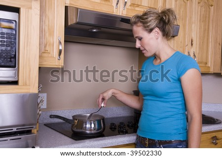 A woman stirring something in her pan on the stove.