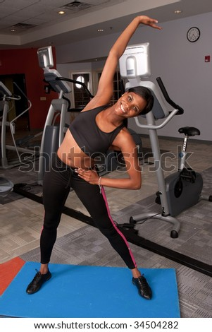 a woman stretches her arm in a gym - stock photo