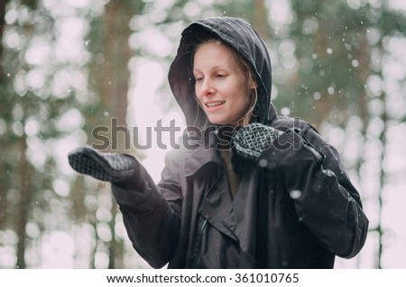 A woman stretching her hand out towards falling snow - stock photo