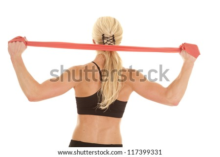 A woman stretching her shoulders with a red band.