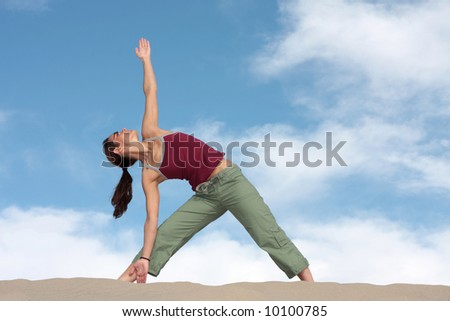 A woman strikes a yoga pose on a sand dune in California - stock photo