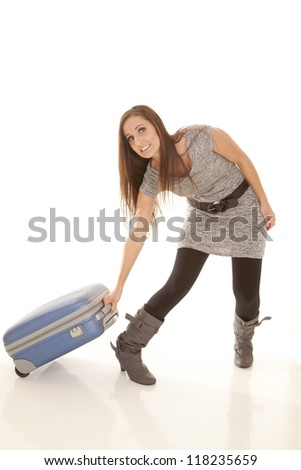 a woman struggling to pull her luggage. - stock photo