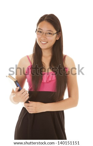 A woman student holding on to her book and pen with a smile on her face.
