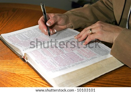 A woman studies a Holy Bible alone at a table (Christian image, shallow focus). - stock photo