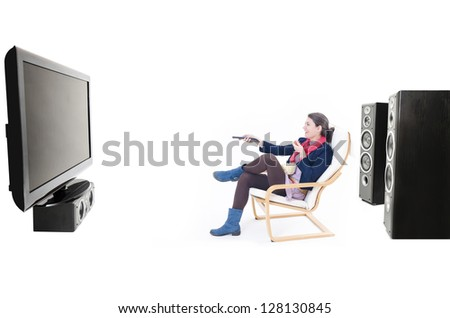 A woman surrounded by speakers watching tv - stock photo