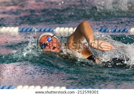 A woman swimming ree style in swimming pool. - stock photo