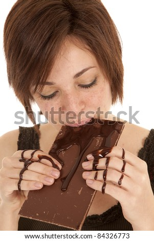 A woman taking a big bite of a chocolate candy bar with chocolate all over her hands. - stock photo