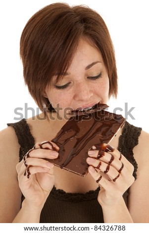 A woman taking a big bite of a chocolate candy bar with chocolate all over her hands.