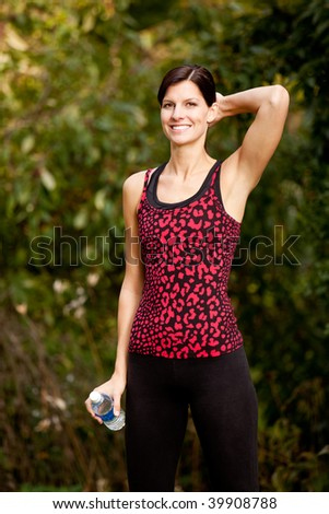 A woman taking a break from exercising in the park - stock photo