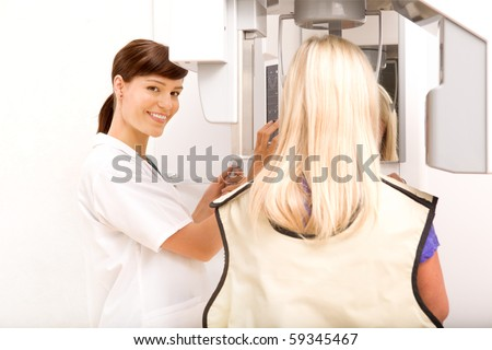 A woman taking a panoramic digital x-ray of a patients teeth - stock photo