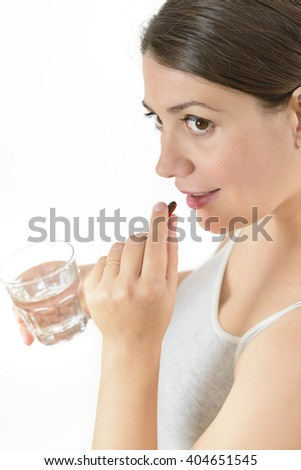 A woman taking a pill isolated on white - stock photo