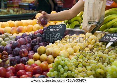 A woman taking fruits in a market - stock photo