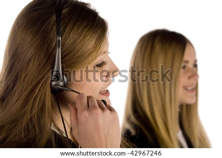 A woman talking on her headset while a co-worker is near by. - stock photo
