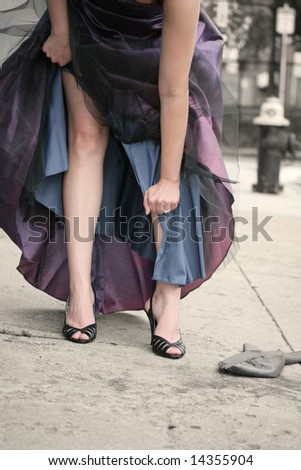 A woman tearing her evening gown in an urban setting