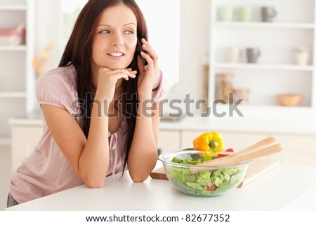 A woman telephoning in the kitchen next to a salad