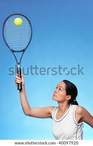 A woman tennis player serving against a blue background. - stock photo