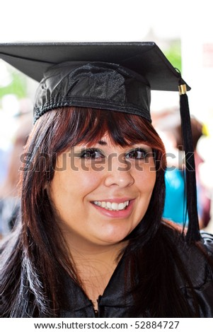 A woman that recently had a university or high school graduation ceremony posing in her cap and gown outdoors.
