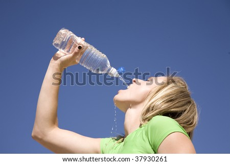 A woman thirsty for water pouring the water in her mouth.