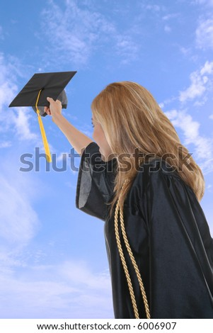 A woman throwing her graduation cap into the air - stock photo