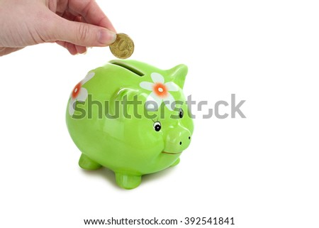 a woman throws a gold coin into a green piggy Bank isolated on white background