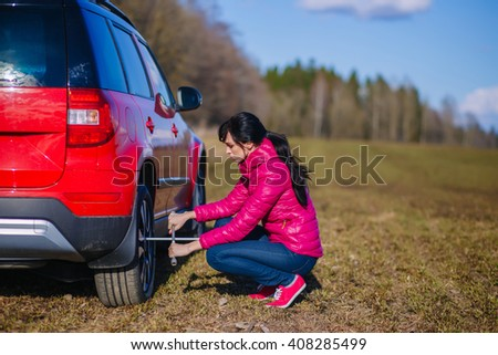 A woman tightening the wheel nuts after changing a flat tire on the spare - stock photo