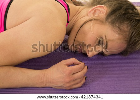 a woman tired after a hard workout, laying on her yoga mat. - stock photo