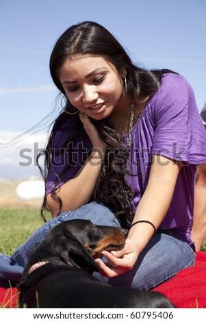 A woman touching a dog outside. - stock photo
