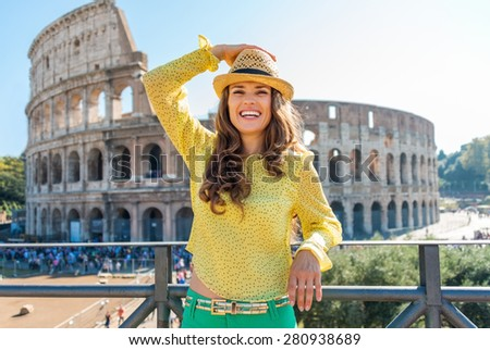 A woman tourist is standing, holding her hat, looking into the distance and laughing. She is delighted to be in Rome. In the distance, the Colosseum and tourists on a hot summer's day. - stock photo