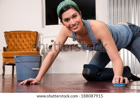 A woman tries to make fun out of cleaning the floor by hand