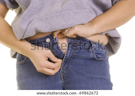 A woman tries to zip up too-tight jeans. - stock photo