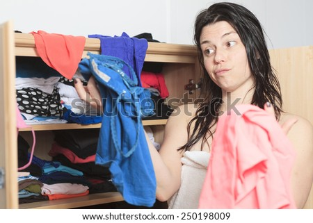 A woman try to choose clothes on her closet - stock photo