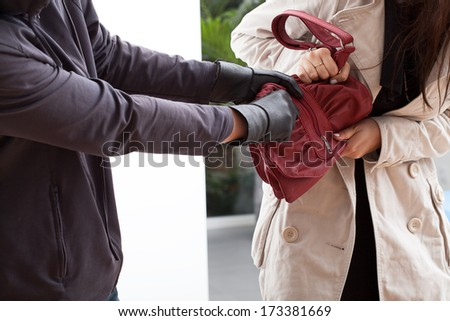 A woman trying not to let a man take her bag - stock photo