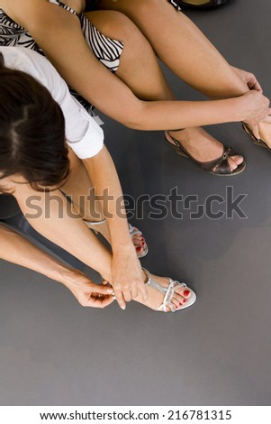 A woman trying on shoes.