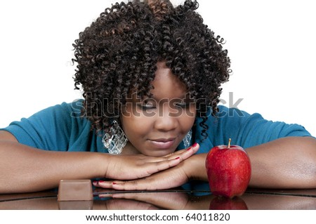 A woman trying to decide whether or not to eat healthy - stock photo