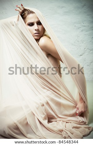A woman trying to get out of the cocoon of beige fabrics - stock photo