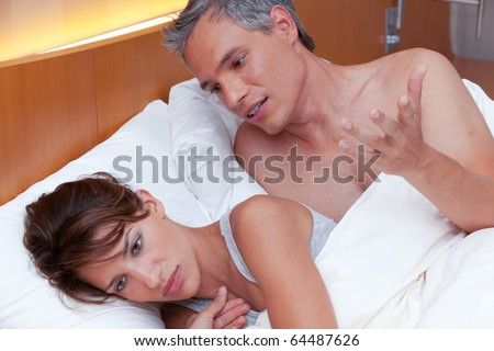 A woman turns her back to her partner as the man tries to talk to her while they argue - stock photo