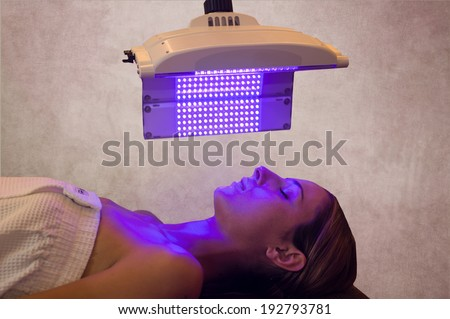 a woman under a light therapy machine, blue light - stock photo