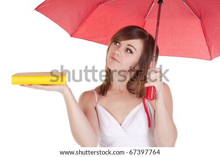 A woman under a red umbrella holding her yellow book out on her hand.