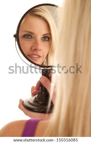 A woman up close looking into a mirror