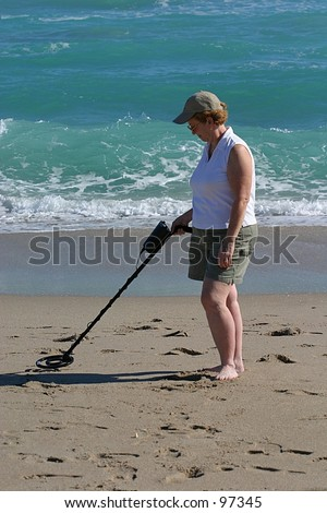 A woman uses a metal detector at the beach. - stock photo